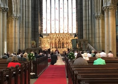 The Vicar blesses a newly married couple during their wedding ceremony. The couple kneel at the front of the Minster aisle surrounded by friends and family.